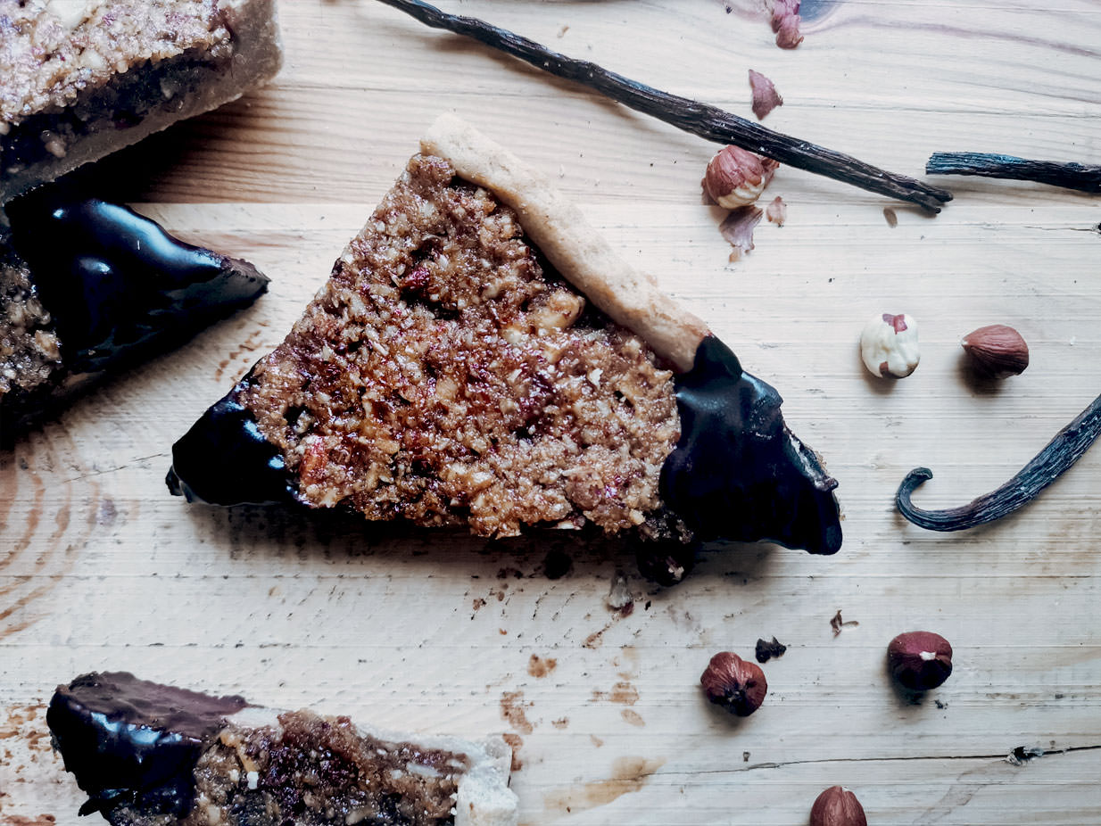 These Roasted Hazelnut Triangles are an indulgent treat. Roasted hazelnuts on a vegan shortcrust pastry with some red currant jelly and chocolate. Sweet, crunchy, and slightly sour thanks to the red currant.